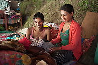 Promila, 18, and Rajib, 20 plays with their three months old son Rajib at Shila Porbot, outskirts of Kathmandu, Nepal. Promila and Rajib lost their home in last month's Nepal earthquake and now they are living in a temporary house in the bank of a river. May 8, 2015