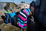 GUGULETU, SOUTH AFRICA - MARCH 12: Women was their laundry at a water point on December 12, 2014, In the Barcelona section of Guguletu, a township outside Cape Town, South Africa. Guguletu is one of the biggest black townships in Cape Town (Photo by Per-Anders Pettersson)