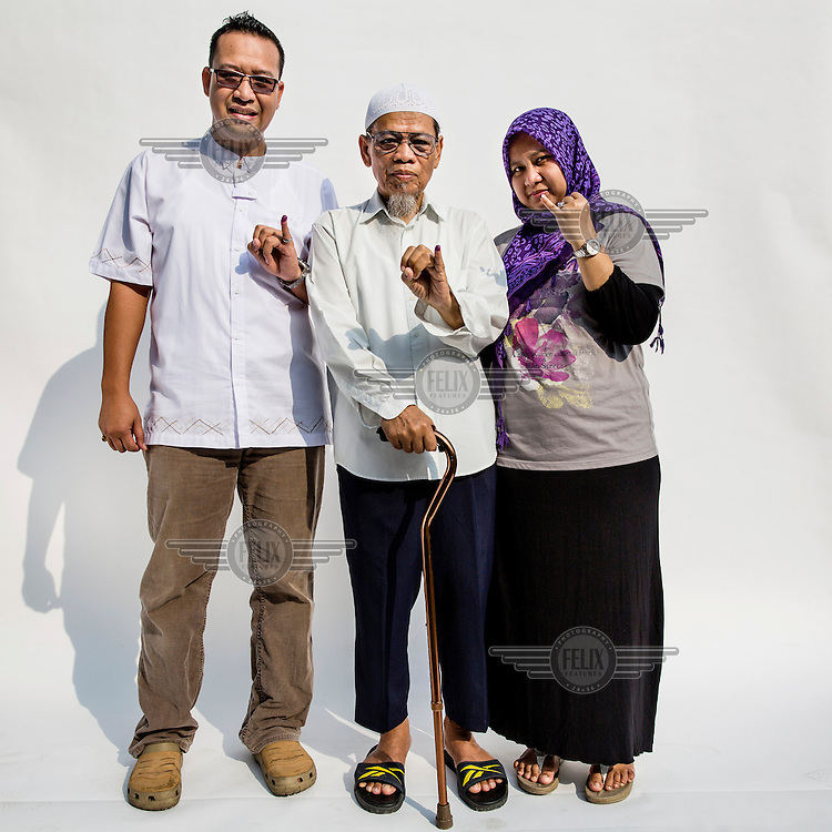 An Indonesian family flash a single finger sign, symbolising Indonesian presidential candidate Prabowo Subianto's candidacy number after they cast their votes at a polling station in Jakarta.