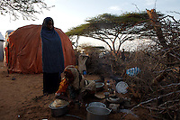 """Ambya Sheik Awi, 14 years old, on right prepares breakfast while her cousin Fartun Yusuf, 13 years, old, stands next to her  in one of the sixteen camps of the KM13 area on the road to Afgooye that host more than 5000 displaced Somalis, who left Mogadishu cause of recent fighting  in war torn Somalia's capital Mogadishu on Wednesday April 23rd 2008.///..Sporadic street fighting between Ethiopian .troops and Islamic fighters trying to bring down Somalia's shaky .government has killed 81 people on April 19 and 20, the head of a .local human rights group said Sunday. .""""The casualties ... were caused by Ethiopians using heavy artillery and .tank shells in residential areas of the war-torn capital. We condemn .this latest fighting,"""" said Sudan Ali Ahmed, chairman of Elman Human .Rights. Besides the 81 dead, 119 people had been wounded, he said. .Reports on Monday April 21 say Ethiopian troops have taken control of a mosque with a large .number of civilians inside following heavy fighting with insurgents. .The reports say a number of civilians were killed inside the mosque and others are being held by Ethiopians against .their will. .This apparent increase in the brutality of attacks may be caused partly by a .recent American decision to classify the Shabab (youth), the Islamic Courts .Union's former military wing, as a terrorist group. Battered by Ethiopian attacks .and by infighting between sub-clans engaged in the insurgency, Shabab .fighters now probably number fewer than 400. But America's decision to .demonise them has boosted jihadist commanders such as Aden Hashi Ayro, .strengthening his reputation for piety and anti-Americanism, which has itself .been boosted by recent missile attacks that have accidentally killed civilians...Philippe Lazzarini, head of the UN Office for the Coordination of Humanitarian Affai .rs (OCHA) Somalia, said on Monday April 21st that the combination of a severe drought, civil insecurity and h .yperinflation was pushing the country to the"""