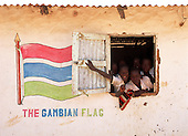 Gambia. Schoolchildren looking out of the window of a school building with the Gambian flag painted on the wall.