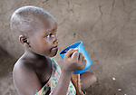 "A girl eats porridge in a care center for orphans and other vulnerable children in Chidyamanga, a village in southern Malawi that has been hard hit by drought in recent years, leading to chronic food insecurity, especially during the ""hunger season,"" when farmers are waiting for the harvest. The ACT Alliance is working with farmers in this village to switch to alternative, drought-resistant crops, as well as using irrigation and other improved techniques to increase agricultural yields. In Chidyamanga, residents have set aside a section of farmland where they work together to grow food especially for the orphans--many of whom lost their parents to AIDS--and other children in the center. Three times a week, the children come to the center, sing and play and eat a nutritious meal."