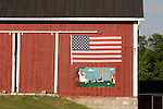 Red barn with American flag and mural.