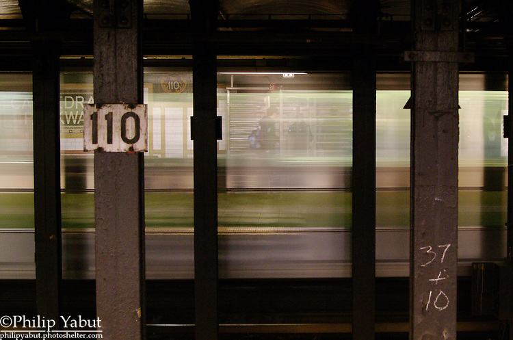A train departs 110th Street Station as passengers leave the concourse.