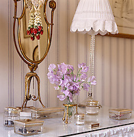 Detail of the dressing table with a matching set of glass vanity boxes with gilt lids and a cut crystal vase of sweet peas