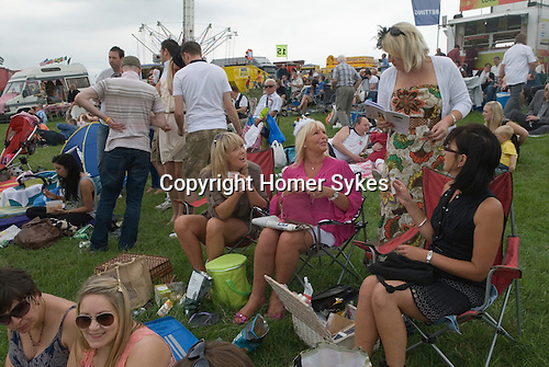 Ladies Day at The Derby horse race. Epsom Down Surrey UK. (l-r) Nina Callan and her auntie Deana Marshall wearing a royal crown to celebrate Queen Elizabeth's diamond jubilee. Plus a group of local friends from Epsom. They are on the Hill.