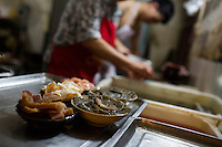 Workers prepare food for an order at Gang Shan Zha Zha, a popular streetside hotpot restaurant on Tiyu Road in central Yuzhong distrist, Chongqing, China. Zhu Zhi Qiang, (19, rear) having worked at the restaurant for four years, said &quot;I want to open a shop like this one day.&quot;<br /> <br /> The restaurant sits on the site of a former neighborhood garbage collection point and &quot;zha zha&quot; is local slang for &quot;garbage.&quot; The restaurant has been open for 5 years and recently opened a second location elsewhere in Chongqing. A manager of the restaurant said that they server 60-70 tables every night, with many tables' bills coming to over 1000RMB. The restaurant often has a long wait. The site is well-reviewed on online restaurant sites similar to Yelp and is known for having good flavor, serving fresh food, and being clean.