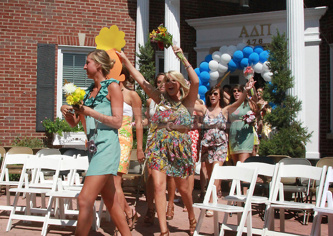 Sisters of the Alpha Delta Pi sorority walk out to their front yard to greet their new pledge class. They celebrated this year's bid day, honoring their pledge class of 2010, on August 20, 2010.