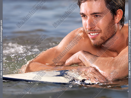 Portrait of a smiling young man with a surfboard in water enjoying summer. Closeup of face.