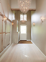 The entrance hallway is lit by a contemporary chandelier and matching wall sconces