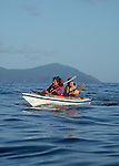 Sea kayaking couple, Queen Charlotte Islands, Haida Gwaii, South Moresby Island, British Columbia, Canada, Tofino Expeditions guides in open water.