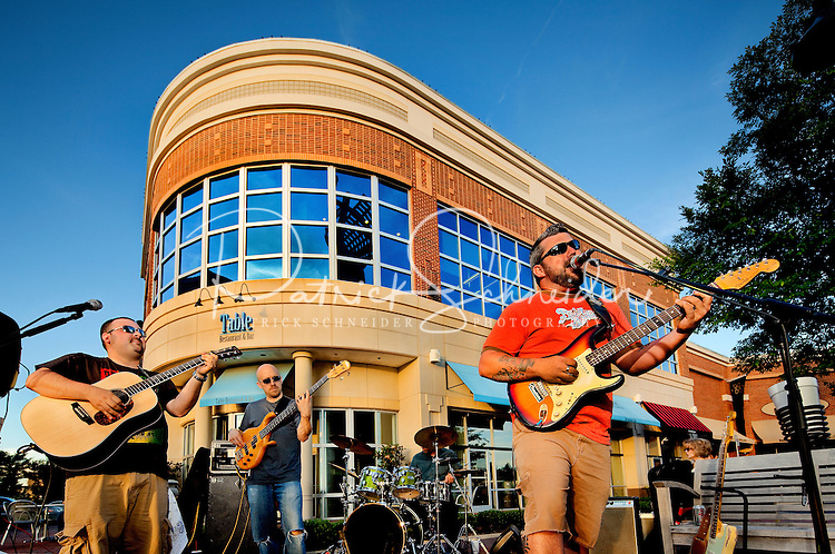 A band of musicians play at the retail shopping center, Ballantyne Village, is located in Ballantyne, a suburban community of Charlotte NC, near the South Carolina border. The 2,000-acre mixed-use development was created by land developer Howard C. Smokey Bissell.