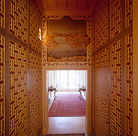 A wall painting of Istanbul is illuminated by  a hidden wall light on a stairwell, which is lined with marquetry built-in cupboards