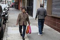 San Francisco Chinatown Una signora di origine cinese passeggia con due borse colorate  A Chinese lady walking with two colored bags