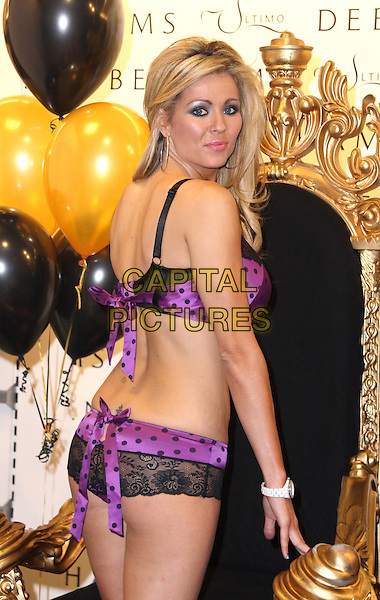 NICOLA McLEAN.Promotes new range of Ultimo lingerie and poses with soldiers from 2 Para inside Debenhams, Colchester, Essex, England. .December 16th 2008.half length black purple bra underwear knickers panties lace polka dot looking over shoulder .CAP/JIL.©Jill Mayhew/Capital Pictures.