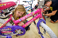STAFF PHOTO BEN GOFF  @NWABenGoff -- 12/03/14 Jazmynn (CQ) Brewer, 7, peels off stickers and packaging on a new bicycle while volunteering with her family from Pineville, Mo. as volunteers assemble and quality check nearly 300 donated bicycles and tricycles in preparation for the NWA United Toys for Joy Christmas Toy Run at Pig Trail Harley-Davidson in Rogers on Wednesday Dec. 3, 2014. Hundreds of bikers will ride from Pig Trail Harley-Davidson to the Benton County Fairgrounds with the bicycles and toys on Dec. 13.