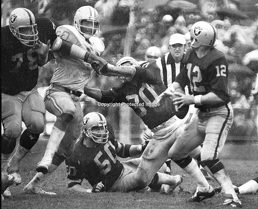 Raider quarterback Ken Stabler is rushed by Detroit Lions         ,Raider blockers Dave Dolby, Mark van Eegan, and Art Shell. (1978 photo/Ron Riesterer)