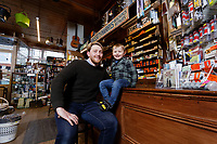 Pictured L-R: Thomas Lewis Jones with his son Arthur Lewis Jones at the counter Hafod Hardware store in Rhayader, mid Wales, UK. Thursday 05 December 2019.<br /> Re: Shop owner Thomas Lewis Jones has made a Christmas advert starring Arthur Lewis Jones, his two-year-old son costing only £100.<br /> Hafod Hardware in Rhayader, Powys, has been making festive adverts for several years.<br /> This year's advert sees Arthur setting up the shop along with members of his family.