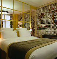 A bedroom is decorated with an elaborate wallpaper and the mirrored wall separates the bed from the bathroom