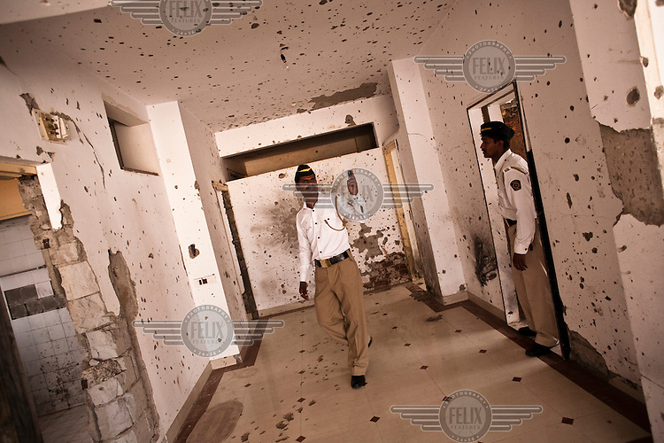 A policeman takes photographs of the bullet riddled walls of Nariman House, headquarters of the Hasidic Jewish group Chabad-Lubavitch, a year after the Mumbai 26/11 terror attacks.