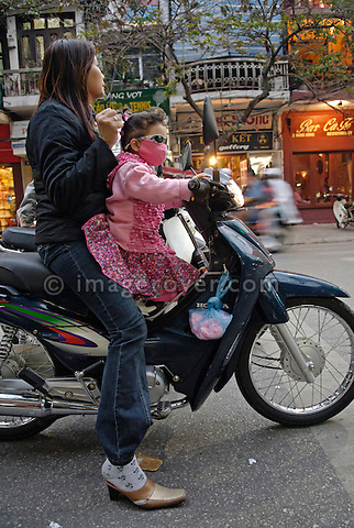 Asia, Vietnam, Hanoi. Hanoi old quarter. Young family on motorbike.