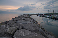 Daybreak over the breakwater at Meaford Harbour, with mirror-still sheltered water harbouring docked sailing yachts.