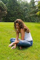 Woman sitting in open field