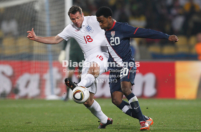 RUSTENBURG, SOUTH AFRICA - JUNE 12:  Jamie Carragher of England (18) and Robbie Findley of the United States (20) do battle during a 2010 FIFA World Cup soccer match June 12, 2010 in Rustenburg, South Africa.  NO mobile use.  Editorial ONLY.  (Photograph by Jonathan P. Larsen)
