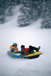 Mother & daughter tubing through fresh snow, Rocky Mtns, CO
