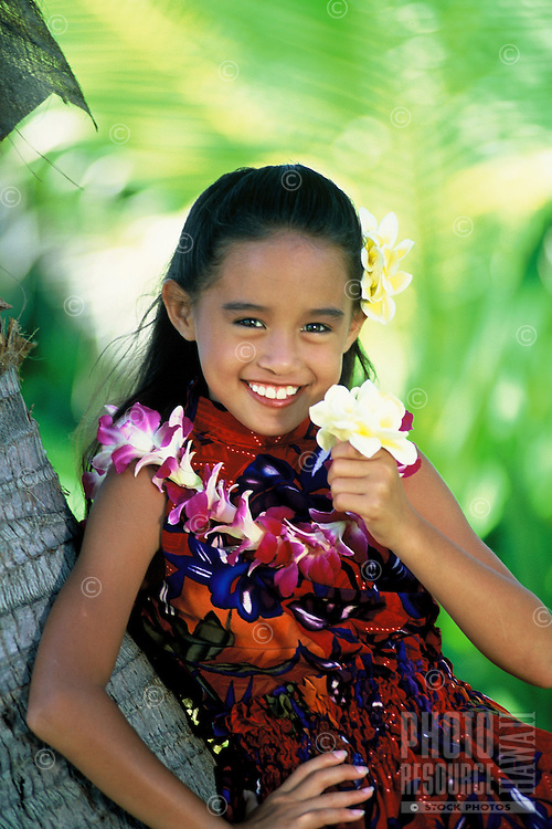 Part Hawaiian girl (age 7) with orchid lei, holding plumeria flowers