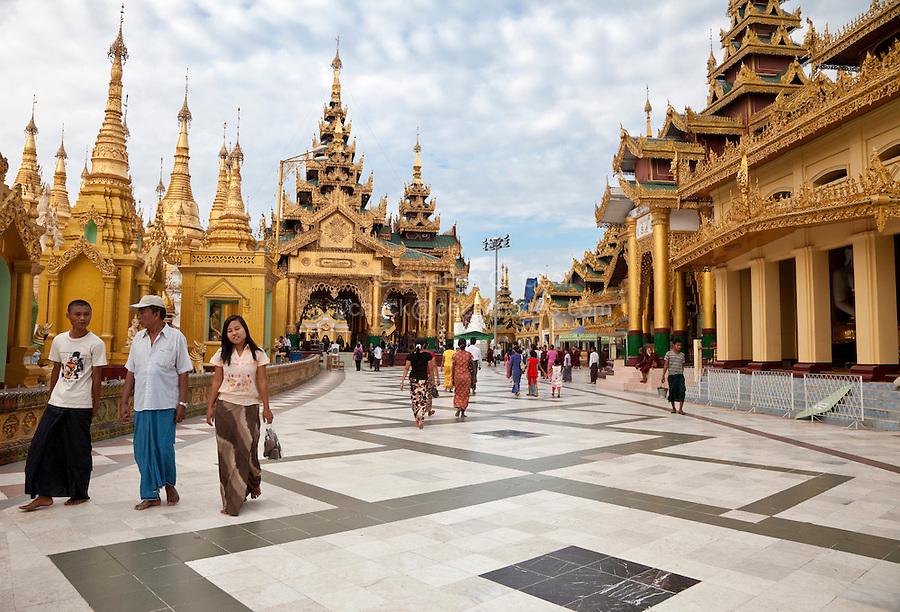 Myanmar, Burma.  Shwedagon Pagoda, Yangon, Rangoon.  Visitors Pass Many Shrines as they Circumambulate the Walkway around the Base of the Stupa.  Two men and woman on left wear the traditional longyi, a wrap-around sarong.