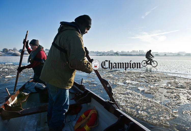 Boatmen breaking ice at Gortglass Lake, Clare, for the annual Christmas Day swim as a man cycles his bike on the frozen lake surface.