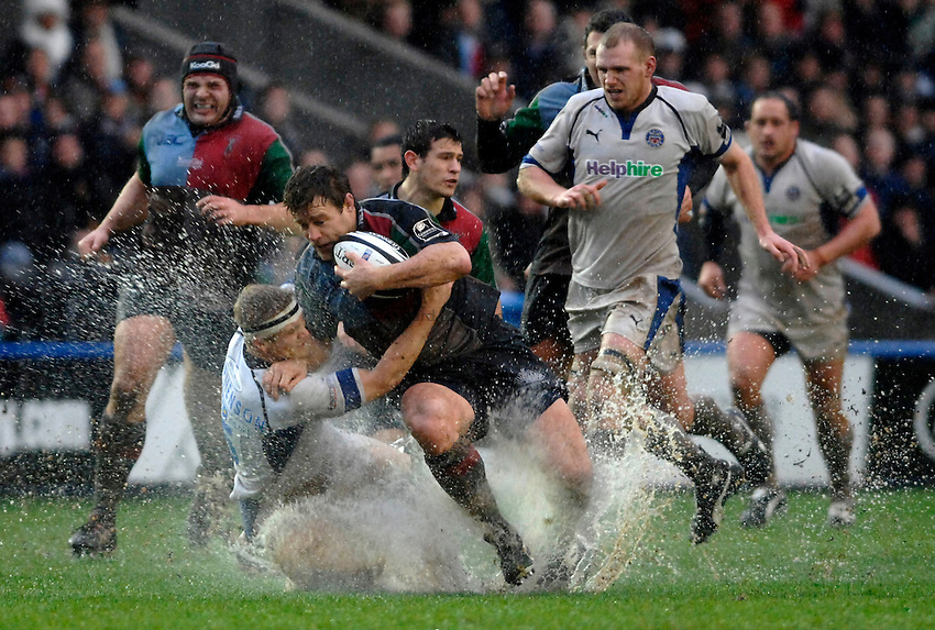 Photo: Richard Lane..NEC Harlequins v Bath Rugby. Guinness Premiership. 06/01/2007. .Quins' captain, Paul Volley is tackled by Bath's Michael Stephenson as water splashes all around.