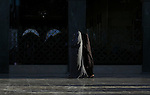Damascus, Syria. 3 Muslim women walking in the courtyard of Sayyidah Zaynab Mosque, at the end of Ramadan. The mosque attracts Shia Muslim pilgrims from Iran and around the world.