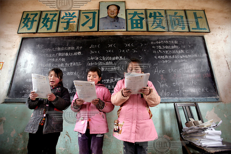 Children from the Morning Tears children's home sing in the village school, under the watchful eye of Chairman Mao and a slogan that reads: