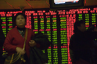 Chinese man walks past an electronic board at the stock exchange in Beijing, China. A weaker dollar in global markets coupled with calls from the US Treasury for faster China exchange rate reforms pushed the yuan to a fresh high against the US dollar recently..01 Feb 2007