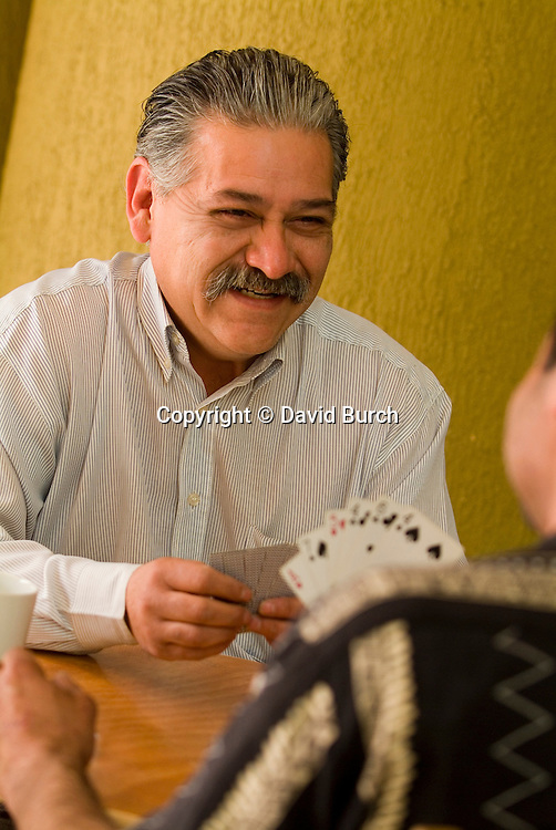 Happy hispanic man  playing cards, close-up