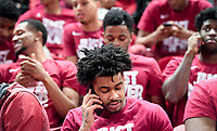 NWA Democrat-Gazette/CHARLIE KAIJO Arkansas Razorbacks guard Anton Beard (center) makes a phone call with teammates after the NCAA selection show announcement, Sunday, March 11, 2018 at Bud Walton Arena in Fayetteville. The Razorbacks will play Butler in Detroit on Friday