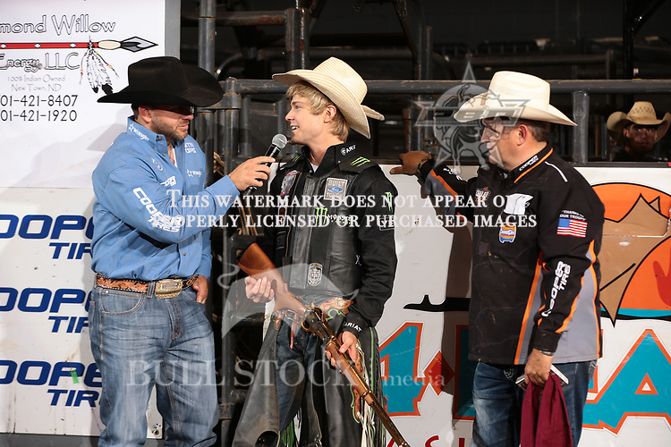 Chad Berger presents Derek Kolbaba with a rifle second day of the Bismarck Real Time Pain Relief Velocity tour PBR. Photo by Andy Watson