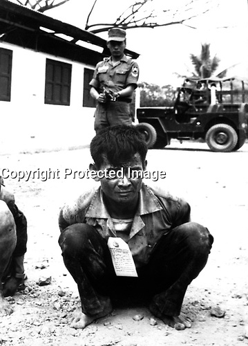 Saigon, South-Vietnam - Feb 1968. <br /> EXACT DATE SHOT UNKNOWN - <br /> Youthful hard-core Viet Cong, heavily guarded, awaits interrogation following capture in the attacks on the capital city during the festive Tet holiday offensive.