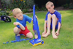 Two brothers with autism playing in garden with toy Hoover.  MR