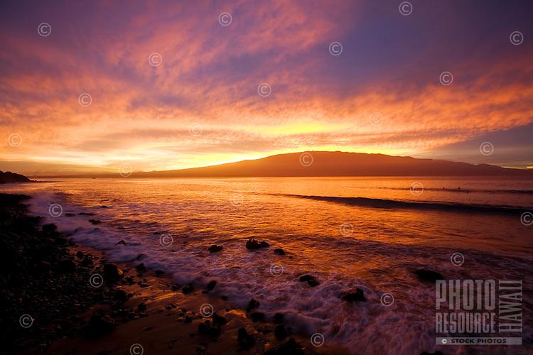 Surfers enjoy a colorful sunrise at McGregor Point, Maui.