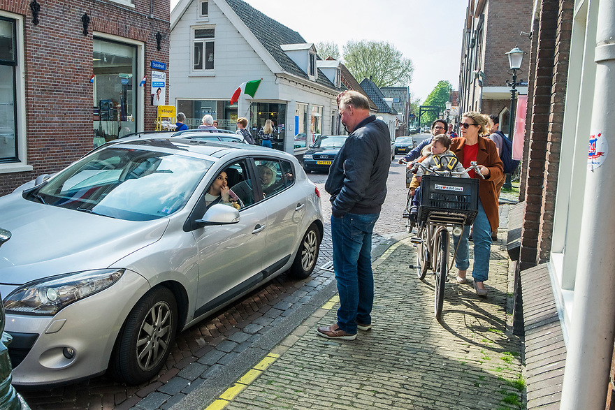 Nederland, Muiden, 20170506<br /> Dorpsleven in smalle straatjes van Muiden. Praatje maken met automobilist.<br /> <br /> Foto: (c) Michiel Wijnbergh