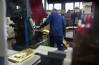 Arezzo: un operaio lamine d'oro all'interno dello stabilimento Chimet. L'azienda recupera metalli preziosi (oro, platino, palladio, iridio, argento) da materiali di scarto come catalizzatori di marmitte, batterie, contatti elettrici di cellulari, computer o materiali di scarto industriale.<br /> <br /> Arezzo: The Chimet company recovers precious metals (gold, platinum, palladium, iridium, silver) from waste materials such as catalysts, mufflers, batteries, electrical contacts to phones, computers or industrial waste materials.