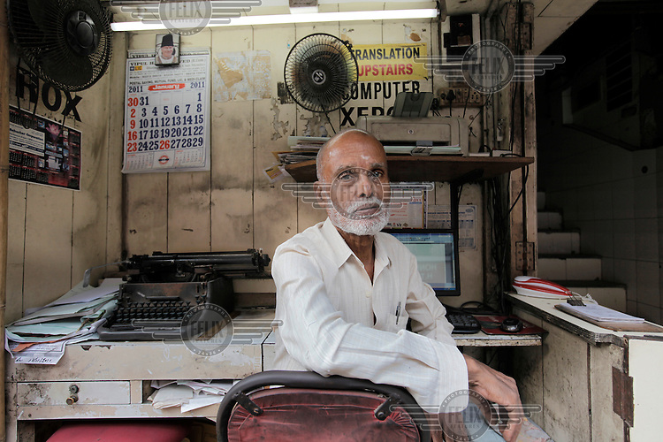 A man offering typing services sits waiting for customers in his street office in central Mumbai.