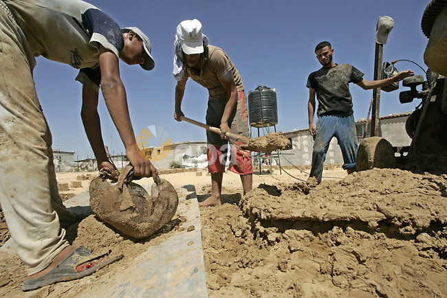 "Palestinian workers prepare blocks of clay for the construction of clay houses to replace houses destroyed in Israel's last military operation in Gaza, in Rafah, southern Gaza Strip on July 02  2009.  Many parts of the Hamas-run Gaza Strip are still in ruins almost after the guns fell silent following Israel's war on the aid-dependent territory. Israel's blockade on Gaza doesn't allow construction material into the Palestinian territory. Amnesty International said on Thursday Israel inflicted ""wanton destruction"" in the Gaza Strip in attacks that often targeted Palestinian civilians during an offensive in December and January in the Hamas-run enclave, in the 117-page report on the 22 days of fighting. Photo By Abed Rahim Khatib"