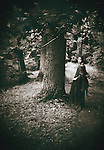 A monochromatic picture of a woman in a vintage gown, standing next to an old tree in a wood or garden.