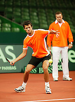6-2-06, Netherlands, Amsterdam, Daviscup, first round, Netherlands-Russia, training, John van Lottum tis training  and behind him the coach Tjerk Bogtstra is looking on
