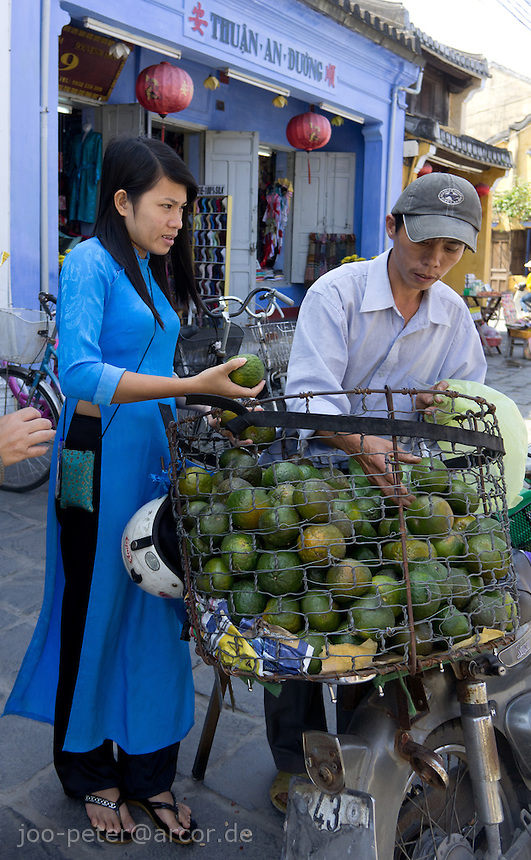 woman buying fruits on the streets of Hoi An, Vietnam
