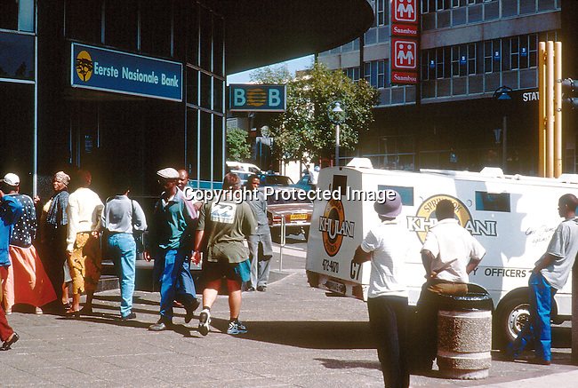PSPOLIC27014.Police.  Cash in transit transfer in Johannesburg.  Security officers load the trunk with cash into van.   People walking past.  3/99..©Per-Anders Pettersson / iAfrika Photos